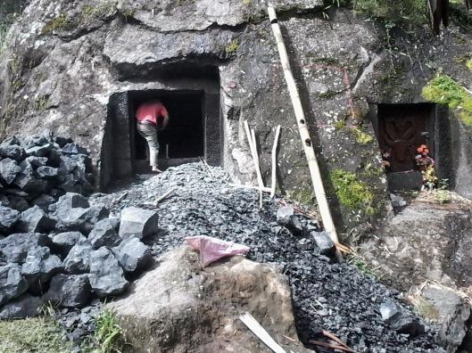 Seorang pekerja sedang memasuki lubang batu yang dibuat untuk tempat jenasah