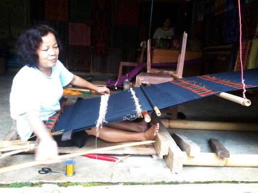 Seorang ibu sedang menenun kain tenun tradisional Toraja